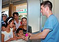 US Navy 100811-N-3589B-051 Hospital Corpsman 2nd Class Joseph Smith, assigned to the guided-missile destroyer USS John S. McCain (DDG 56), hands out toys to patients while filling prescriptions during a medical civic action pro.jpg