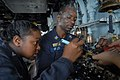 US Navy 110809-N-DU438-265 Electrician's Mate 3rd Class Rashan Ferguson, left, and Chief (Select) Electrician's Mate Dale Holder solder wires in a.jpg