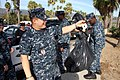 US Navy 111113-N-OM503-008 Operations Specialist 1st Class David Pacheco, from Tularosa, N.M., weighs the last bag of trash collected from East Bea.jpg