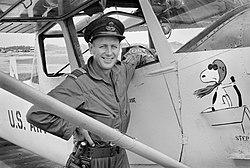 Smiling man in overalls with peaked cap next to aircraft featuring image of Snoopy as the Red Baron