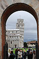 View of Pisa Cathedral (Duomo di Pisa) (forefront), The Leaning Tower of Pisa (background) through an arch in the Medieval walls surrounding Piazza dei Miracoli. Pisa, Tuscany, Central Italy.jpg
