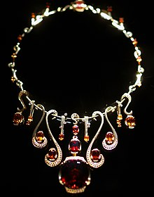 Colour photograph of a 22 carat yellow gold necklace with large deep red Malaya Garnet as center stone, flanked by pave diamonds and garnets varying from deep red to bright orange.