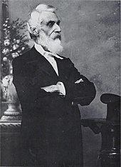 a man with a white beard and hair faces right, with his arms folded. He is dressed in a suit of a sort worn in the late 19th century.