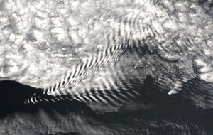 Orographic lift - A gravity wave cloud pattern—analogous to a ship wake—in the downwind zone behind the Île Amsterdam, in the far southern Indian Ocean. The island generates wave motion in the wind passing over it, creating regularly spaced orographic clouds. The wave crests raise and cool the air to form clouds, while the troughs remain too low for cloud formation. Note that while the wave motion is generated by orographic lift, it is not required. In other words, one cloud often forms at the peak. See wave cloud.