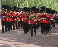 The band of the Welsh Guards, wearing red uniforms and busbies, march up the Mall towards Buckingham Palace