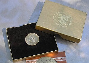 A gold medallion in a box, including a lid and a piece of paper