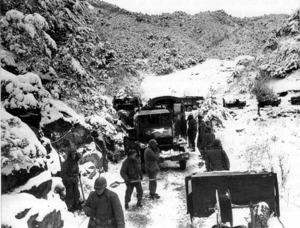 A group of soldier shoving snow in front of a convoy