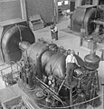 Workman checks the steam pressure on the turbine of the first steam generator in the steam and power plant of the Polymer Rubber Corporation facility (36130819893).jpg