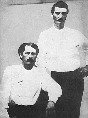 Bat Masterson - Deputies Bat Masterson (standing) and Wyatt Earp in Dodge City, 1876: The scroll on Earp's chest is a cloth pin-on badge