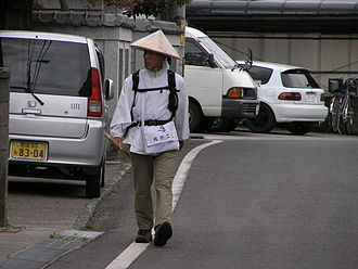 Shikoku Pilgrimage - An aruki-henro or walking pilgrim, marked out by his distinctive sedge hat, white shirt, and kongō-zue. The henro-michi route passes through the countryside and a number of cities.