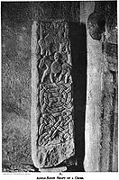 A rectangular stone, stood on one end, with carvings of a man on a horse, another horse, geometric designs and some letters.