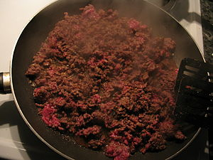 Beef being cooked in a frying pan. It has been...