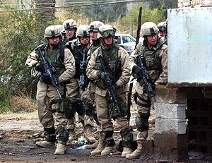 325th Infantry Regiment (United States) - Members of the regiment waiting to dash across a street in Baghdad, Iraq, as part of their mission there searching for suspected militants.