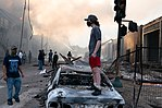 A man stands on a burned out car on Thursday morning as fires burn behind him in the Lake St area of Minneapolis, Minnesota (49945886467).jpg