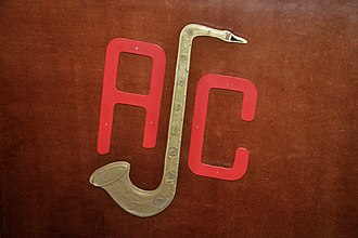 Antwerp Jazz Club (AJC) - A sculpture resembling the logo of the Antwerp Jazz Club, attached to the front of the foldable wooden screen covering the presenter's area, present during the jazz club's Tuesday-evening sessions in its clubhouse (13 September 2016).