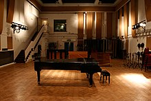 A colour image of a large room with a piano in the middle