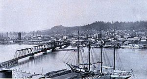 Steamboats of Grays Harbor and Chehalis and Hoquiam Rivers - Waterfront of Aberdeen, Washington in 1912, along the Chehalis River, showing a four-masted schooner loading lumber, and on the north side of the river, a sternwheeler moored at a dock