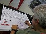 """Academia da Força Aérea (AFA) em Pirassununga-SP-Brasil. O primeiro astronauta brasileiro, o bauruense Marcos Pontes dando um autógrafo em um banner no Domingo Aéreo 2015 no """"Ninho das - panoramio.jpg"""