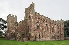 A ruined building minus a roof and with crumbling walls. Some of the walls are crenelated. The walls are build with red stones in the middle and grey stones as edging on the tops and corners