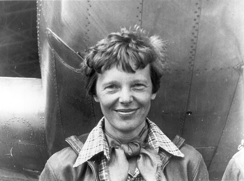 Amelia Earhart standing under nose of her Lockheed Model 10-E Electra, small