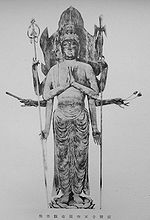 Front view of a standing statue with robes four pairs of arms. Each pair is almost left-right symmetric. Two hands are placed as in prayer with palms facing each other in front of the body. Other pairs of arms are in various positions holding flowers, a short object shaped like a flute, a necklace and long pole weapons. There is a large halo behind the head of the statue.