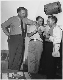 Three men talking. The one on the left is wearing a tie and leans against a wall. He stands head and shoulders above the other two. The one in the center is smiling, and wearing an open-necked shirt. The one on the right wears a shirt and lab coat. all three have photo ID passes.