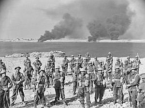 A group of soldiers stand on a foreshore. In the background, smoke billows