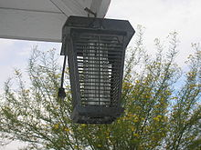 bug zapper hung on a house corner. Black Bedroom Furniture Sets. Home Design Ideas