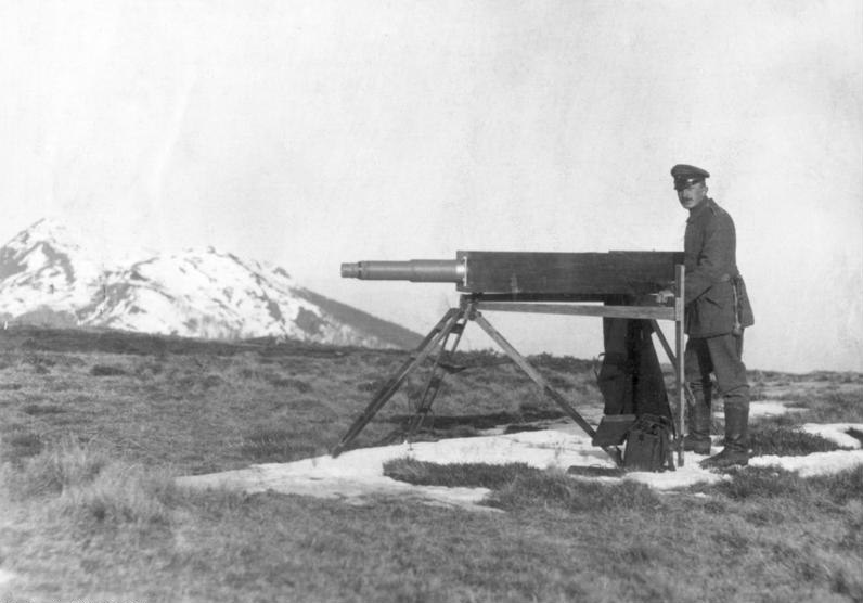 Soldier standing next to a Telescopic instrument on a tripod.