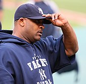 A dark-skinned man in a navy-blue sweatshirt and baseball cap grabs the brim of his cap with his left hand.