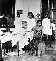 COLLECTIE TROPENMUSEUM Een Europeaan vaccineert Indonesische patiënten met neosalvarsaan tegen de ziekte framboesia TMnr 10006691