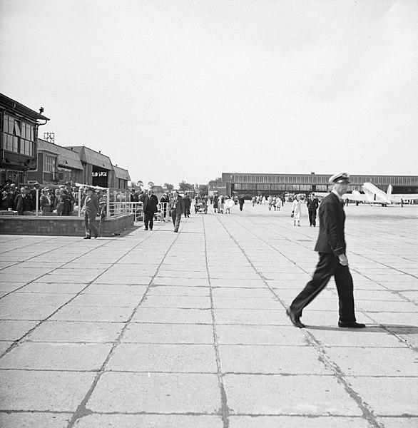 File:Café-terras De wijde blik met op de achtergrond de grote hangar op luchthaven , Bestanddeelnr 254-2419.jpg
