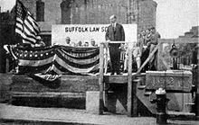 Coolidge se tient sur une estrade décorée par des drapeaux américains.