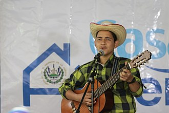 Culture of El Salvador - Young Salvadoran man singing and playing guitar