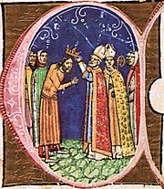 A bishop puts a crown on the head of a bearded man.