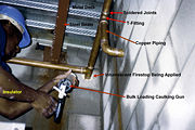 Copper piping system in a building with intumescent firestop being installed by an insulator, Vancouver, British Columbia, Canada.