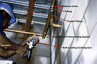 Copper piping system with intumescent firestop being installed by an insulator in Vancouver, Canada.