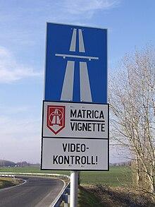 Segnale di inizio autostrada in Ungheria integrato da un pannello che ricorda l'obbligo della vignetta e segnala che il percorso è video controllato