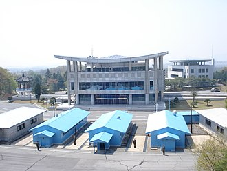 Inter-Korean Peace House - Viewed toward the south: North Korean soldiers stand guard among the United Nations Command conference buildings (painted blue) and the North Koreans' conference buildings (painted white) that straddle the demarcation line bisecting Panmunjom Truce Village. Grounds are tan-colored on the North Korean side, grey-colored on the South Korean side, with a low concrete curb positioned along the demarcation line between. To the rear is the Freedom House. Further rear and to the right is Peace House.