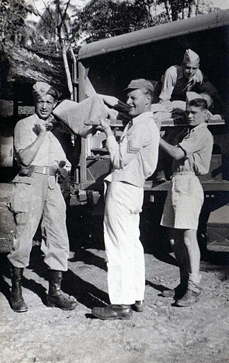 First Division 7 December - Soldiers of the 7 December Division carry a wounded soldier out of an ambulance in the Dutch East Indies