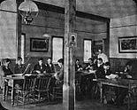 A room with tables, chairs, and men seated