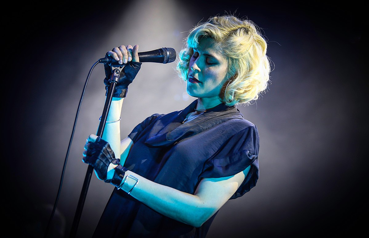 A photo of the singer Dessa, a pale white woman with platinum blonde hair that is short and slightly curly, holding a microphone