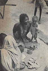 Old photograph of a woman squatting and tiny, emaciated toddler standing on a sidewalk. The woman is shirtless but squatting to conceal her breasts. The toddler is wearing rags.