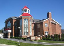 A large brick building of irregular polygonal shape rests amid a green lawn with ornamental shrubbery by a curving paved driveway. An ornamental lamp post rises above the driveway, and a United States flag rises on a pole near the building and opposite the lamp post. The building's bell tower rests on a two-story base fitted with elaborate arched windows.