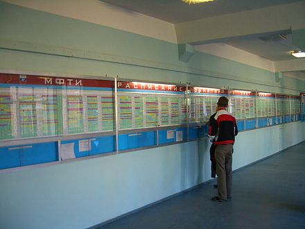 Moscow Institute of Physics and Technology student examines the university's main class schedule board on the first day of classes to find what classes he - and all students in his specialization (sub-major) - will attend this semester. E7331-MFTI-Glavny-Korpus-schedule.jpg