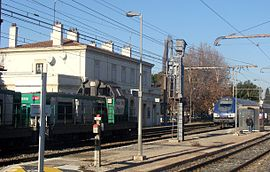 Rognac railway station, with a passing freight train and an Intercity-TER