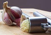 Garlic being crushed using a garlic press.