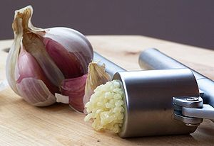 A garlic press, with pressed garlic.