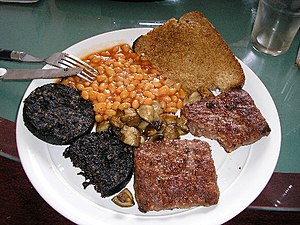 Blood sausage - British-style cooked breakfast, centred around black pudding (left), served with square sausage, baked beans, mushrooms, and fried bread