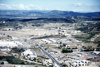 An aerial view of the naval base with the Navy Exchange and McDonald's at left and an outdoor movie theater at bottom right, 1995 Guantanamo Bay Navy Exchange and BEQ.jpg
